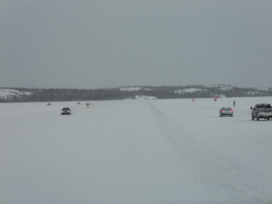 Cars, snowmobiles and people on the ice road